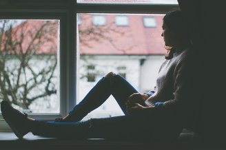 A woman sitting on a window sill looking out the window