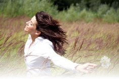 A woman happily running through a meadow